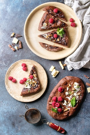 Whole and slised homemade dessert chocolate pizza with different chocolates, raspberries and mint served on ceramic pale with cloth and ingredients above over blue texture background. Top view, space.