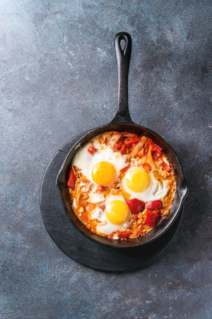 Traditional Israeli Cuisine dishes Shakshuka. Fried egg with vegetables tomatoes and paprika in cast-iron pan on wooden board over blue texture background. Top view, space.