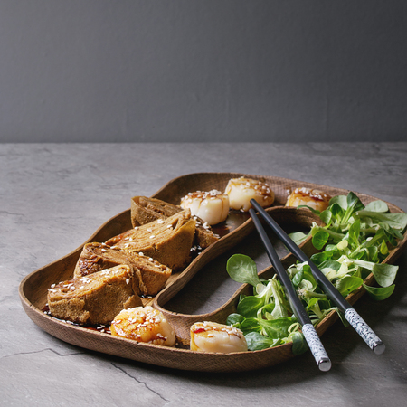 Asian style fried scallops with Japanese Rolled Omelette Tamagoyaki and soy sesame sauce in wooden plate with green salad, chopsticks over gray texture table. Copy space. Square images