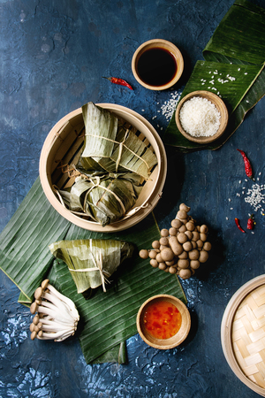 Asian rice piramidal steamed dumplings from rice tapioca flour with meat filling in banana leaves served in bamboo steamer. Ingredients and sauces above over blue texture background. Top view, space. Banco de Imagens - 99734532