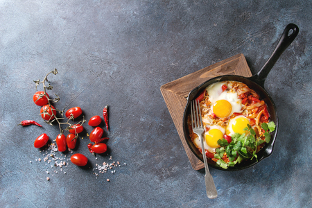 Traditional Israeli Cuisine dishes Shakshuka. Fried egg with vegetables tomatoes and paprika in cast-iron pan on wooden board with coriander herbs over blue texture background. Top view, space.