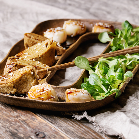 Asian style fried scallops with Japanese Rolled Omelette Tamagoyaki and soy sesame sauce in wooden plate with green salad, chopsticks over textile linen background. Close up. Square images