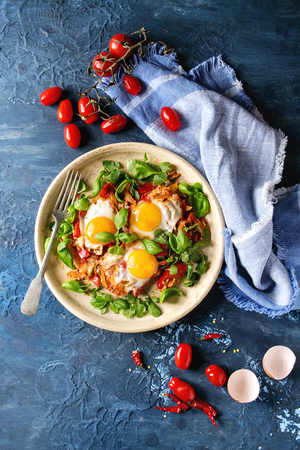 Traditional Israeli Cuisine dishes Shakshuka. Fried egg with vegetables tomatoes and paprika in ceramic plate with cloth, herbs and ingredients above over blue texture background. Top view, space. Stock Photo - 99734548