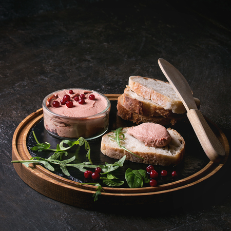 Chicken homemade liver paste or pate with sliced whole grain bread, wood knife, cranberries, green salad served in glass jar on wooden slate serving board over dark texture background. Square image
