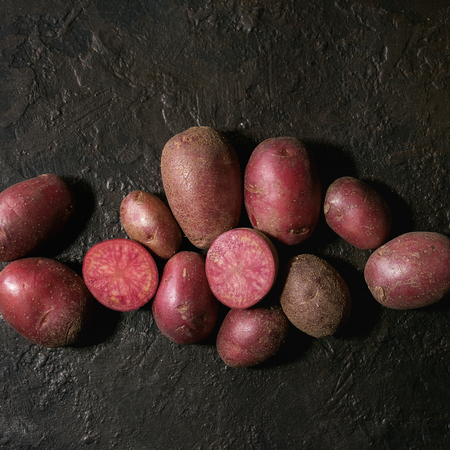 Raw uncooked organic potatoes named lilu rose, whole and slice over dark texture background. Top view, space. Square images