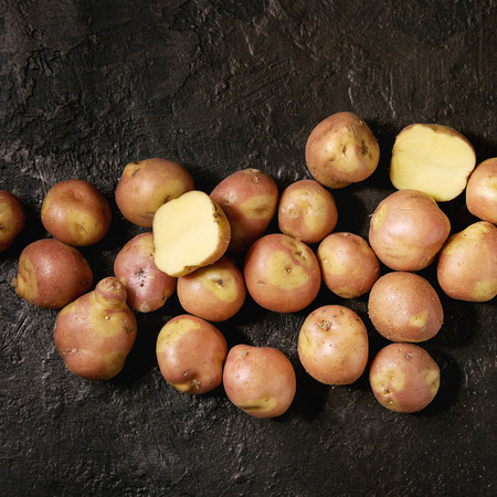 Raw uncooked organic potatoes named miss blush, whole and slice over dark texture background. Top view, copy space. Square image Banco de Imagens
