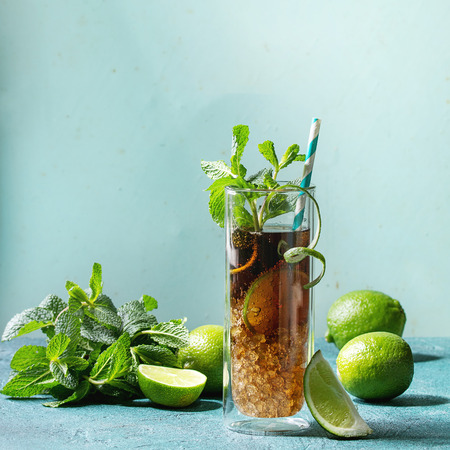 Glass of classic Cuba libre cocktail with lime, mint, crushed ice and cola, served with ingredients above and retro cocktail tubes over turquoise green pin-up style background. Square image, space