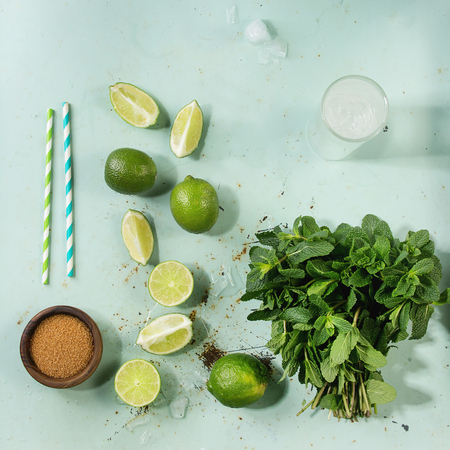 Ingredients for making mojito cocktail. Bundle of fresh mint, limes, brown sugar, crashed ice cubes, glass of soda water, tubes over green pin up background. Top view. Food knolling. Square image