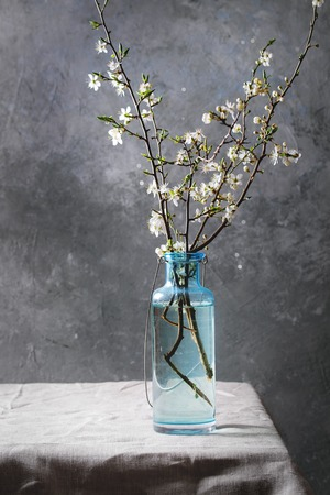 Spring white pear blooming branches in blue glass bottle standing on table with linen tablecloth.