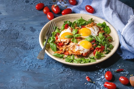 Traditional Israeli Cuisine dishes Shakshuka. Fried egg with vegetables tomatoes and paprika in ceramic plate with cloth, herbs and ingredients above over blue texture background. Copy space. Stock Photo