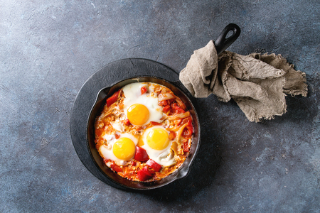 Traditional Israeli Cuisine dishes Shakshuka. Fried egg with vegetables tomatoes and paprika in cast-iron pan on wooden board with cloth over blue texture background. Top view, space.