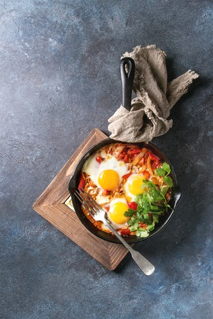 Traditional Israeli Cuisine dishes Shakshuka. Fried egg with vegetables tomatoes and paprika in cast-iron pan on wooden board with cloth and herbs over blue texture background. Top view, space. Stock Photo
