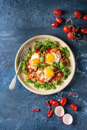 Traditional Israeli Cuisine dishes Shakshuka. Fried egg with vegetables tomatoes and paprika in ceramic plate with herbs and ingredients above over blue texture background. Top view, space. Stock Photo