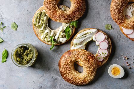 Variety of homemade bagels with sesame seeds, cream cheese, pesto sauce, eggs, radish, herbs served on crumpled paper with ingredients above over grey texture background. Top view, space. Stok Fotoğraf