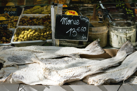 Market stall with dry salted cod fish and vegetables at Parisian street farmers market.