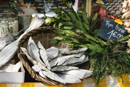 Market stall with dry salted cod fish, herbs and vegetables at Parisian street farmers market.