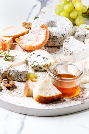 Cheese plate assortment of french cheese served with honey, walnuts, bread and grapes on white wooden serving board over white marble texture background. Close up Фото со стока