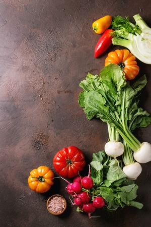 Variety of wet raw fresh organic colorful vegetables tomatoes, radish with leaves, fennel, paprika with bowl of pink salt for salad over dark brown texture background. Top view, space. Stock Photo