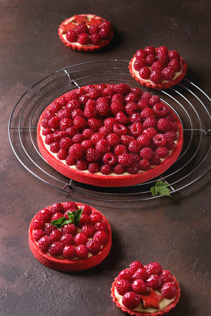 Variety of red raspberry shortbread tarts and tartlets with lemon custard and glazed fresh raspberries served on cooling rack over dark brown texture background. 写真素材