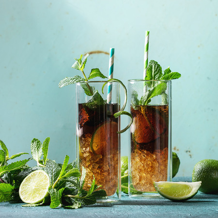 Two Glasses of classic Cuba libre cocktail with lime, mint, crushed ice and cola, served with ingredients above and retro cocktail tubes over turquoise green pin-up style background. Square image