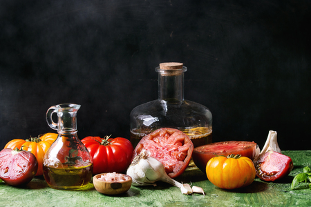 Still life with variety of red and yellow organic tomatoes with olive oil, garlic, salt for salad over green table with black background. Copy space. Zdjęcie Seryjne - 101283922