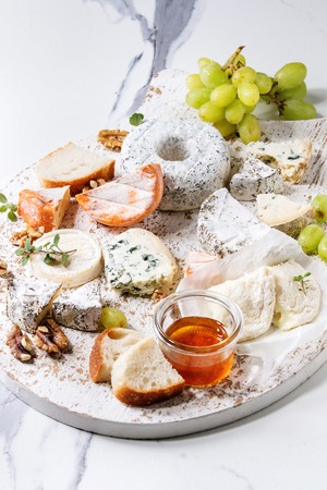 Cheese plate assortment of french cheese served with honey, walnuts, bread and grapes on white wooden serving board over white marble texture background. Close up 写真素材