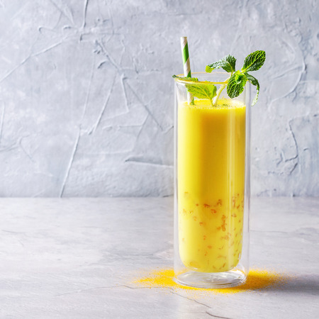 Cup of ayurvedic drink golden coconut milk turmeric iced latte with curcuma powder, crushed ice, mint over grey kitchen table. Copy space. Square image