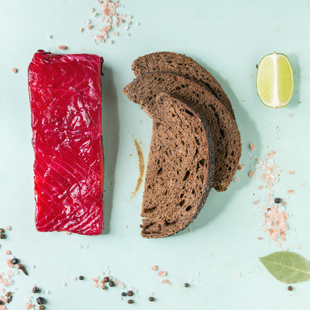 Piece of beetroot marinated salted salmon with sliced rye bread, pink salt, pepper and lime over light green pin-up style background. Top view, space. Food knolling. Square image Stock Photo