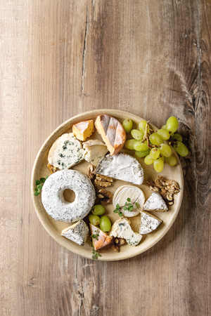 Cheese plate assortment of french cheese served with walnuts and grapes on ceramic plate over wood texture background. Top view, copy space.