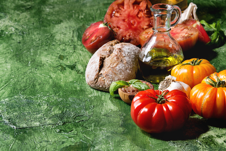 Variety of red and yellow organic tomatoes with olive oil, garlic, salt and bread for salad or bruschetta over green texture background. Close up, copy space. Stock Photo