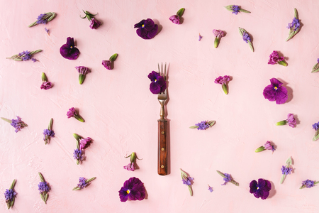 Variety of purple edible flowers for dish decorating with vintage fork over pink pastel background. Top view, space. Archivio Fotografico - 101498909