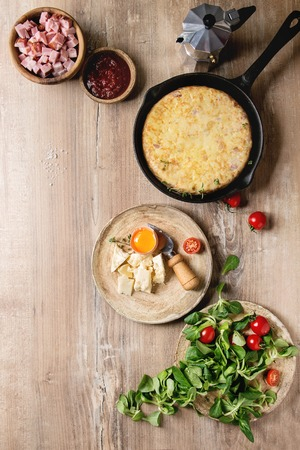 Spanish potato omelette tortilla with bacon served in cast-iron pan with sauce and ingredients above over wooden background. Top view, space.