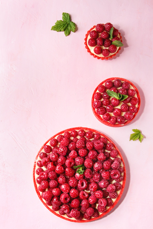 Variety of red raspberry shortbread tarts and tartlets with lemon custard and glazed fresh raspberries over pink pastel background. Top view, space. Stock fotó