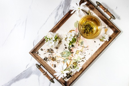 Glass cup of hot green tea on vintage tray with spring flowers white magnolia and cherry blooming branches over white marble texture background. Top view, space. Stock Photo