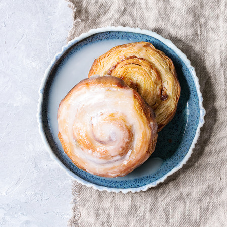 Homemade glazed puff pastry cinnamon rolls with custard and raisins on blue plate over grey texture background with textile linen. Top view, copy space. Square image