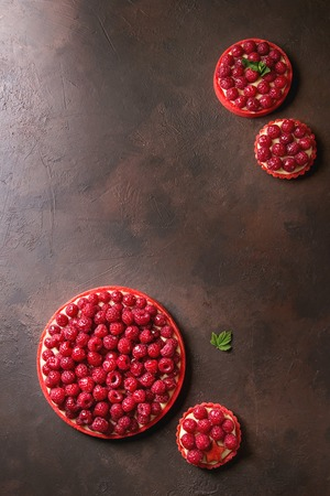 Variety of red raspberry shortbread tarts and tartlets with lemon custard and glazed fresh raspberries over dark brown texture background. Top view, space.