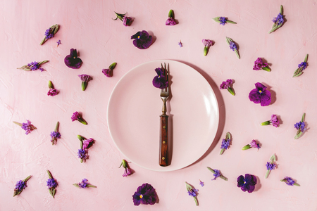 Variety of purple edible flowers for dish decorating with empty ceramic plate and fork over pink pastel background. Top view, space.