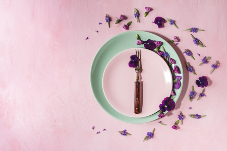 Variety of purple edible flowers for dish decorating with empty ceramic plate and fork over pink pastel background. Top view, space. Archivio Fotografico - 101499100