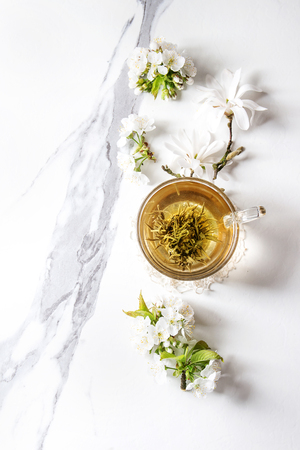 Glass cup of hot green tea with spring flowers white magnolia and cherry blooming branches over white marble texture background. Top view, copy space.