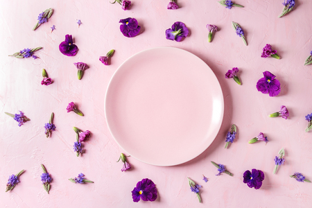Variety of purple edible flowers for dish decorating with empty ceramic plate over pink pastel background. Top view, space.