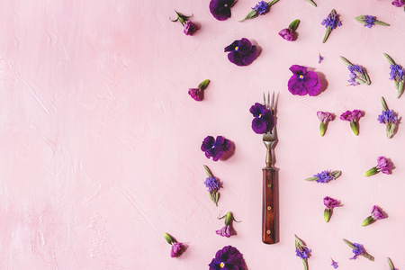 Variety of purple edible flowers for dish decorating with vintage fork over pink pastel background. Top view, space. Archivio Fotografico - 101499124