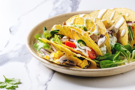 Variety of vegetarian corn tacos with vegetables, green salad, chili pepper served on ceramic plate with tomato and cream sauces with ingredients above on white marble kitchen table. Close up Banco de Imagens