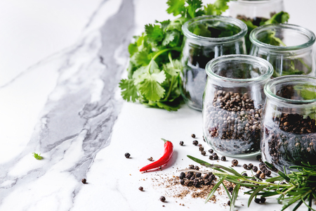 Variety of different black peppers allspice, pimento, long pepper, monks pepper, peppercorns and ground powder in glass jars with chili pepper and fresh herbs on white marble kitchen table. Standard-Bild - 101983236