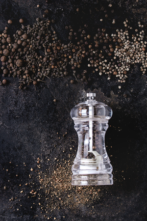 Variety of different black peppers allspice, pimento, long pepper, monks pepper, peppercorns and ground powder from transparent pepper mill over old black iron texture background. Top view, space. Standard-Bild - 101983247