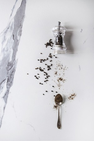 Black peppers peppercorns and ground powder from transparent pepper mill to spoon over white marble texture background. Top view, space.