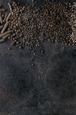 Variety of different black peppers allspice, pimento, long pepper, monks pepper, peppercorns over old black iron texture surface. Food background. Top view, space. Standard-Bild - 101983312