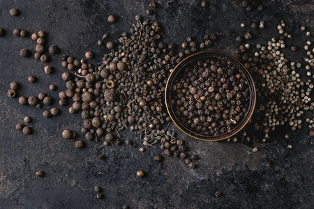 Variety of different black peppers allspice, pimento, monks pepper, peppercorns and ground powder in tin can over old black iron texture background. Top view, space. Standard-Bild - 101983327