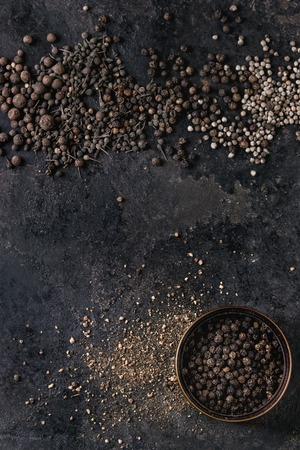 Variety of different black peppers allspice, pimento, monks pepper, peppercorns and ground powder in tin can over old black iron texture surface. Top view, space. Food background Standard-Bild - 101983333