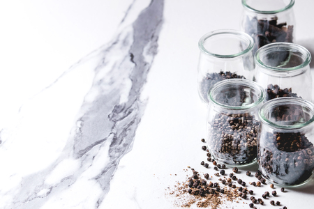 Variety of different black peppers allspice, pimento, long pepper, monks pepper, peppercorns and ground powder in glass jars on white marble kitchen table. Standard-Bild - 101983335