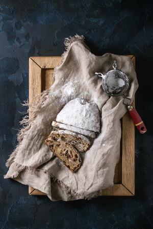 Geschnittener Weihnachtskuchen, traditionelles deutsches festliches Backen. Vollkornstollen mit Rosinen und Zuckerpulver auf Leinenserviette, Holztablett, Vintage-Sieb über dunkelblauem Hintergrund. Draufsicht, Raum